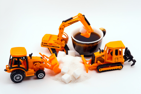 toy construction machines loads cube sugar into a real cup of coffee on a light background