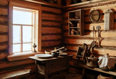 Fragment des Inneren einer alten Bauernblockhütte - ein Tisch mit Holz- und Keramikgeschirr, eine Petroleumlampe Standard-Bild