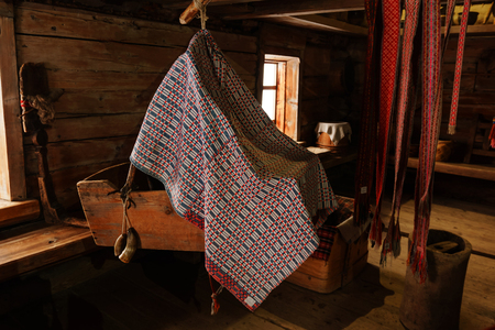 fragment of the interior of an old peasant log cabin with a cradle, distaff and woven patterned belts