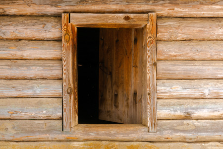 background - ajar wooden door in the log wall Imagens
