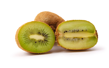 three ripe kiwi fruit (two of them cut) close up on white background 写真素材