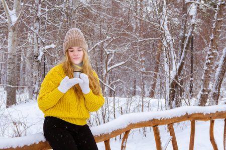 girl in a sweater holding a cup  with a hot drink in a winter park