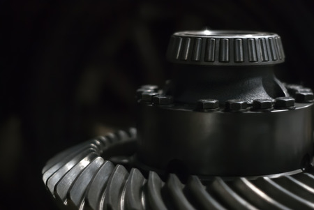 massive metal detail - shaft with tapered roller bearing and spiral bevel gear wheel - on a dark background