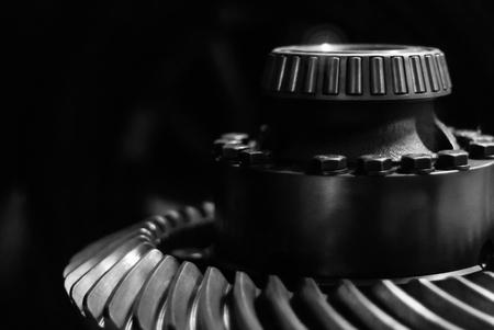 Detalle de metal masivo - eje con rodamiento de rodillos cónicos y rueda dentada cónica en espiral - sobre un fondo oscuro