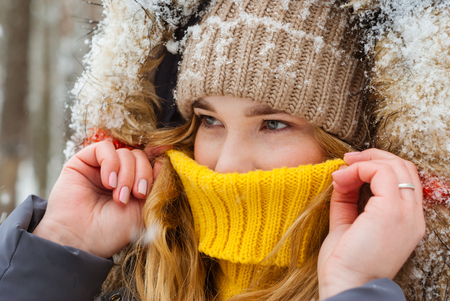 portrait of a girl warming up with her breath, hiding her nose in the collar of a warm sweater, close-up Banco de Imagens