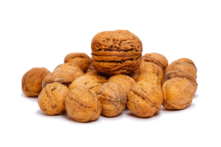 heap of walnuts, one of which is more than the others, isolated on a white background