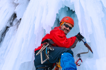 smiling male rock climber with ice ax among icicles of a frozen waterfall Standard-Bild