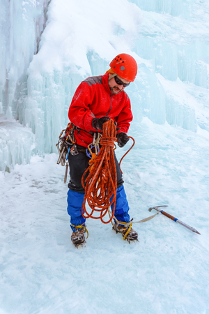 ice climber standing on the snow under the glacier is preparing a rope for climbing