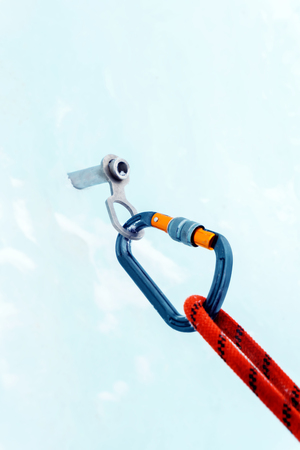 Ice climbing anchor with ice screw, safety rope and carabiner, closeup