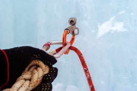 Ice climbing anchor with ice screw, safety rope, carabiners and climber`s arm, closeup