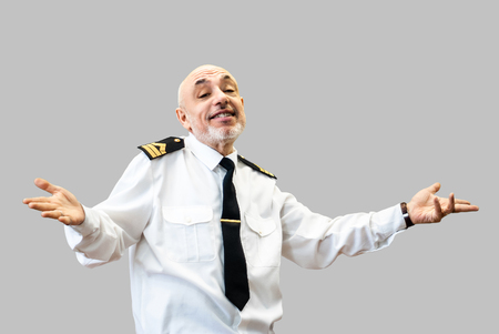 happy elderly man in an officer's sea uniform smiles and shrugs; isolated on gray background Banco de Imagens