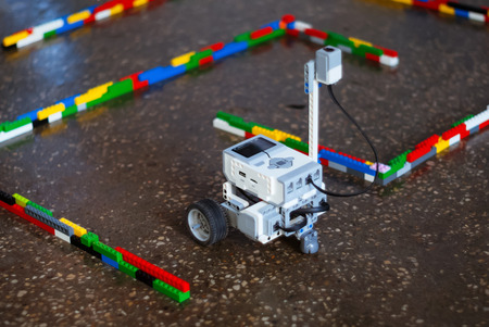 small real programmable robot on wheels moves through an artificial labyrinth