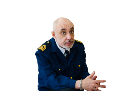 elderly man in an officer's sea uniform the sailor looks thoughtfully at the camera, thinking about something, fingers crossed, isolated on white background