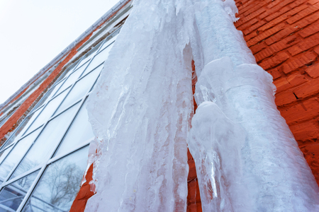 huge icicle on the red brick wall of the building, soft focus, perspective Standard-Bild