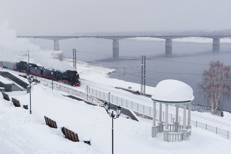 winter snowy landscape with steam locomotive moving along the river bank with a vintage rotunda and automobile bridge in the background