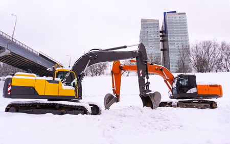 two bright tracked excavators are parked on a snowy field, booms and sticks form an enfilade
