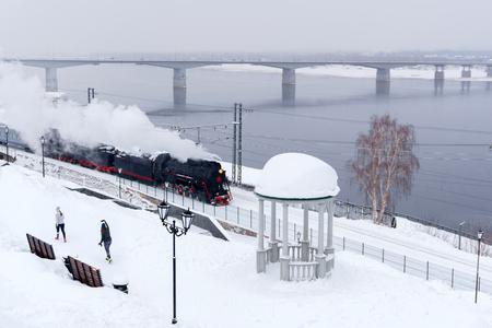 winter snowy landscape with steam locomotive moving along the river bank with a vintage rotunda and automobile bridge in the background, female joggers in the foreground photograph it with a smartphone Archivio Fotografico