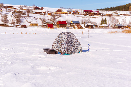 equipment for ice fishing - tent-shanty, hand auger and sleigh - stand on the ice against the backdrop of a winter rural landscape