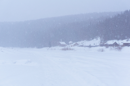 small village on the bank of a frozen winter river during a thick snowstorm