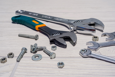 Adjustable spanners and ordinary wrenches, nuts and bolts are on the table close up