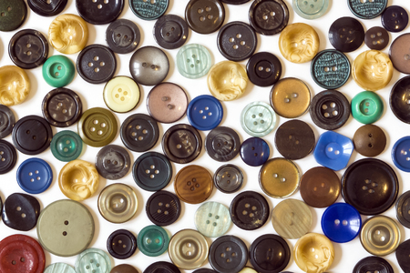 background - multicolored plain buttons chaotically arranged on a white surface