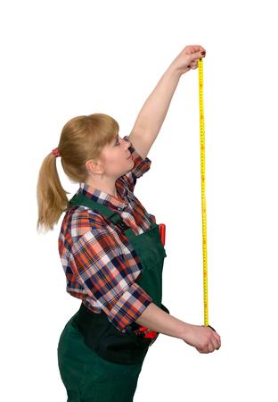 Mujer joven en monos de trabajo sosteniendo una cinta métrica tensionada aislado sobre fondo blanco.