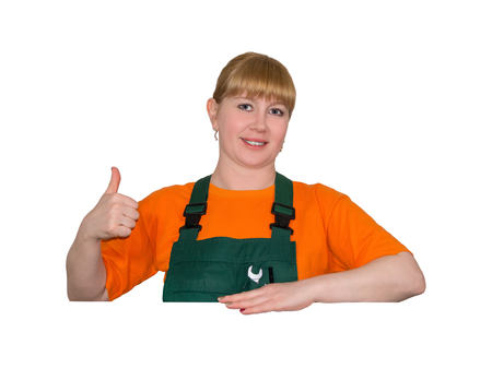 young woman in a work overalls holds thumb up, standing over empty space without inscriptions, isolated on white background