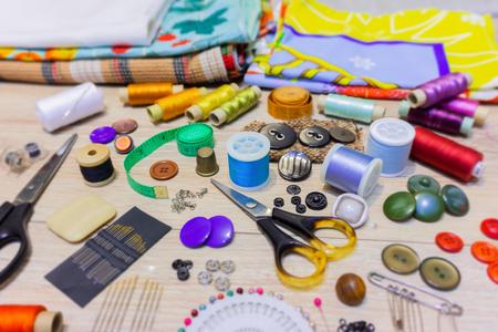 Varios accesorios para coser y bordar se encuentran en el primer plano de la mesa con fondo borroso y primer plano Foto de archivo