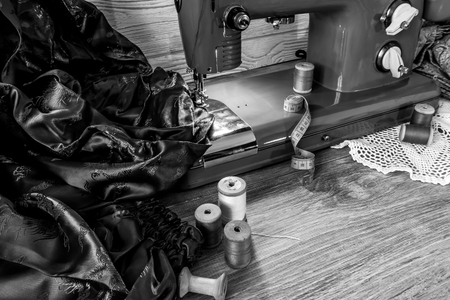 monochrome still life with vintage electric sewing machine, cloth and thread
