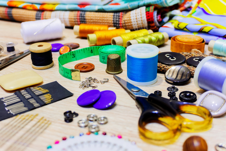 various accessories for sewing and needlework lie on the table close-up with blurred background and foreground