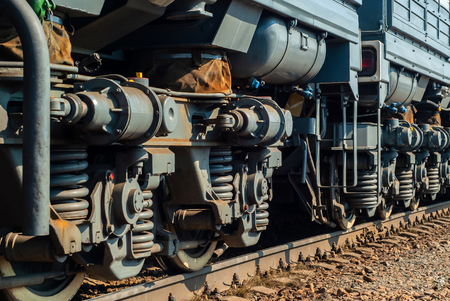 fragment of a sunlit modern locomotive on a track with truck frames extending into perspective