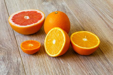 martwa natura - różne całe i pokrojone owoce cytrusowe na jasnej drewnianej powierzchni stołu z desek Zdjęcie Seryjne