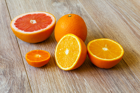 still life - various whole and cut citrus fruits on a light wooden plank table surface Stockfoto