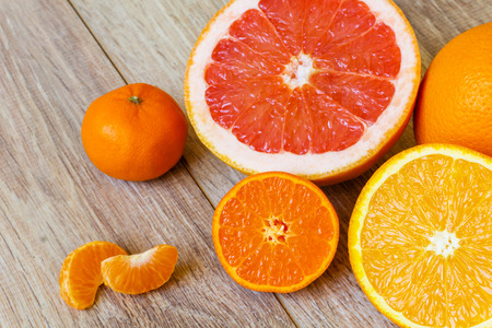 still life - various whole and cut citrus fruits on a light wooden plank table surface