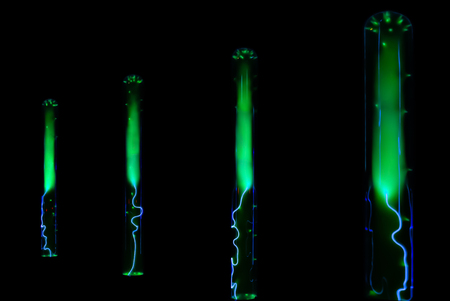 lightning and green glowing of electrical discharges in flasks with inert gas on a black background 免版税图像