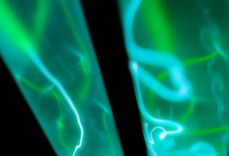 abstract neon background - lightning and green glowing of electrical discharges in flasks with inert gas on a black background