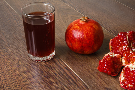 stil life - red whole and cutted pomegranate fruits, scattered seeds and glass with juice on a dark wooden tabletop