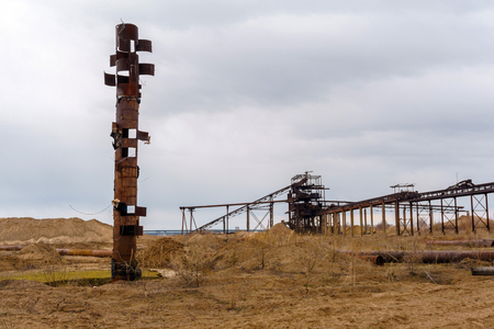 desert industrial landscape with stationary rusty gravitational separator of sand and gravel, strange rusty pipe resembling a totem pole on the foreground