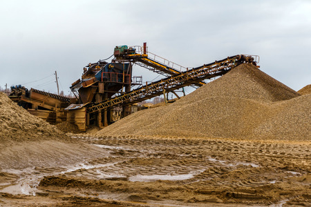 desert industrial landscape with stationary rusty gravitational separator of sand and gravel on the horizon