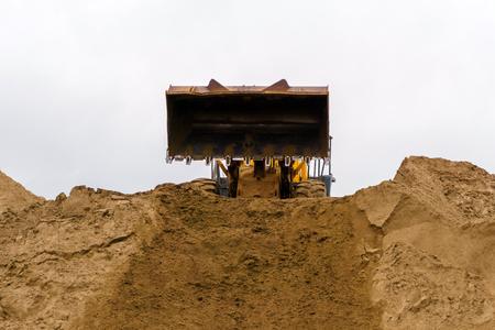 El cucharón del cargador acaba de descargar la arena en la parte superior del montón de arena. Foto de archivo