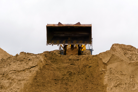 loader bucket has just unloaded the sand on top of sandy heap Stock Photo