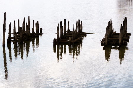 beautiful water landscape with fragments of piles of destroyed bridge, reminiscent of unknown hieroglyphs