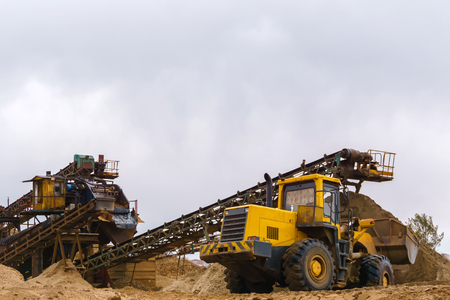 stationary rusty gravitational sand and gravel separator and bucket loader on the background