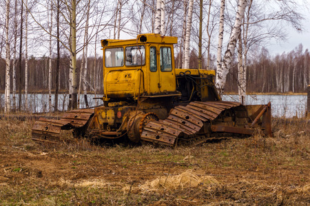 broken rusty bulldozer with a torn tracks stands in a spring grove near the lake