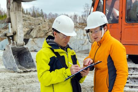 Un hombre y una mujer trabajadores con cascos firman un documento con el trasfondo de equipos de construcción en una cantera