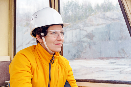 woman in a hard hat and goggles in the cab of heavy construction equipment Imagens