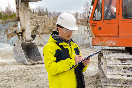 man geologist or a mining engineer writes something in a map-case amid a quarry with construction equipment