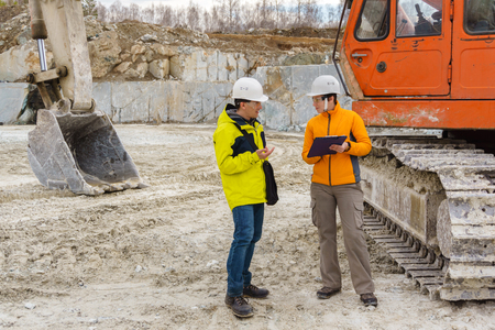 a man and a woman workers or geologists in helmets discuss something against the background of construction equipment in a quarry