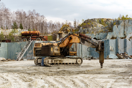 excavator-mounted hydraulic jackhammer stands in a quarry for the extraction of marble