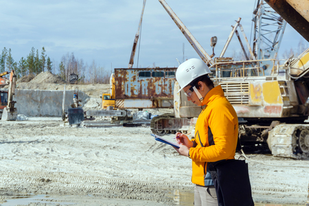 female geologist or a mining engineer writes something in a map-case amid a quarry with construction equipment